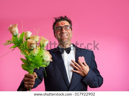 Nerd man with lipstick marks on face in Valentines Day and flowers - stock photo