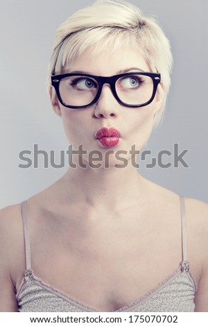 Nerdy and thinking girl with horned glasses. Naturally toned. - stock photo