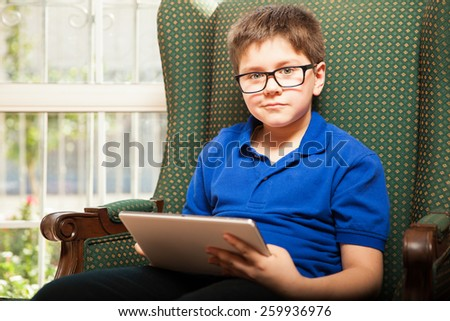 Nerdy blond boy relaxing at home and using a tablet computer - stock photo
