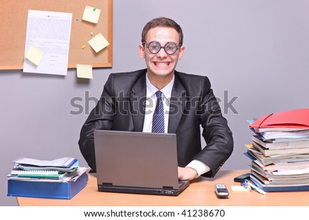 Nerdy businessman working on a laptop in the office - stock photo