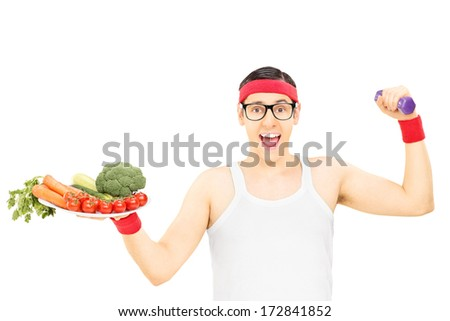 Nerdy guy holding plate with vegetables and a dumbbell isolated on white background - stock photo