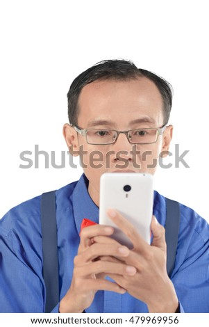 Nerdy man holding cellphone and look concentration. Isolated over white background