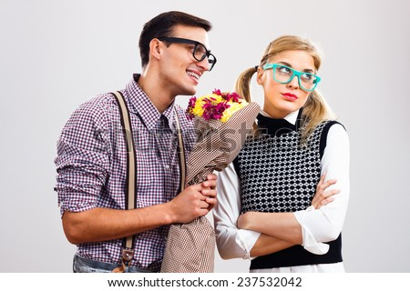 Nerdy man is giving  a bouquet of flowers to his girlfriend,he had made a mistake and he is hoping that she will forgive him,Please forgive me my dear! - stock photo