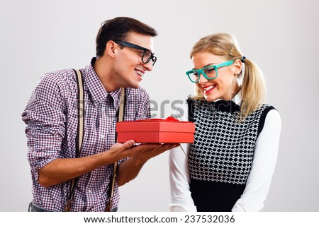 Nerdy man is giving a present to his nerdy lady,Gift for my nerdy lady! - stock photo