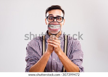 Nerdy man is holding loupe and showing his teeth with braces.I have braces and I am still handsome! - stock photo