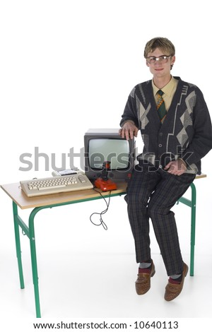 Nerdy man sitting on table next to old-fashioned computer. Smiling and looking at camera. Front view, white background. Whole body - stock photo