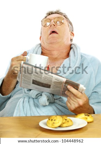 Nerdy middle aged man falls asleep at the breakfast table with a cup of tea and muffins. - stock photo