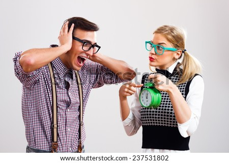 Nerdy woman is showing to her boyfriend that time is passing by and he very frustrated,Time - stock photo
