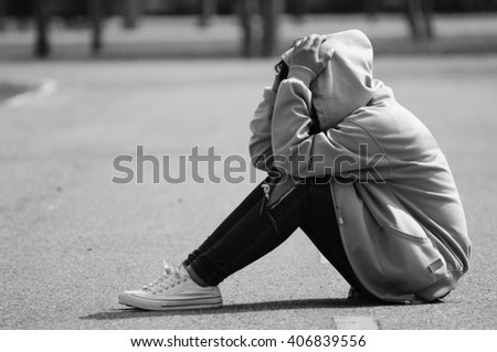 Nervous and Fearful Girl Sitting on the Road - stock photo