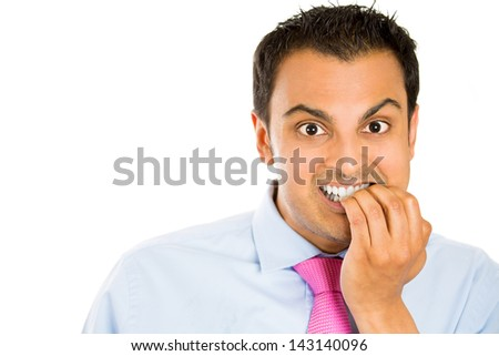Nervous businessman biting his fingernails with teeth, isolated on white background with copy space to left - stock photo