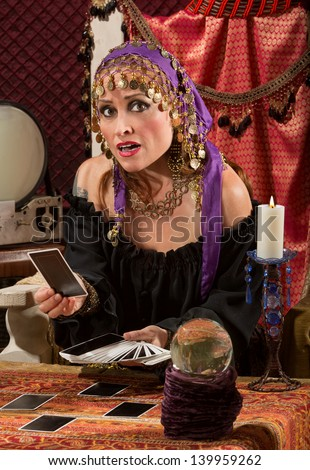 Nervous Caucasian female fortune teller with tarot cards - stock photo
