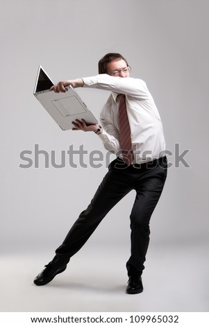 Nervous manager trying to break his laptop - stock photo