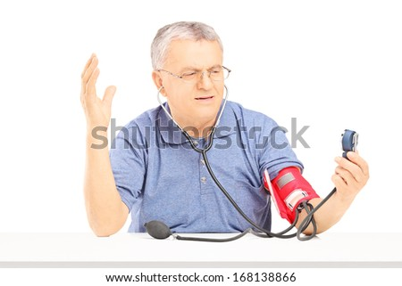 Nervous senior man measuring blood pressure with sphygmomanometer and gesturing with his hand isolated on white background - stock photo