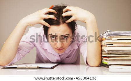 nervous woman working with documents (psychological portrait, aggression, anger, frustration) - stock photo