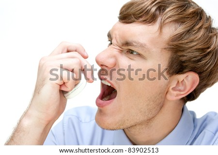 nervous young businessman swearing on the phone - stock photo