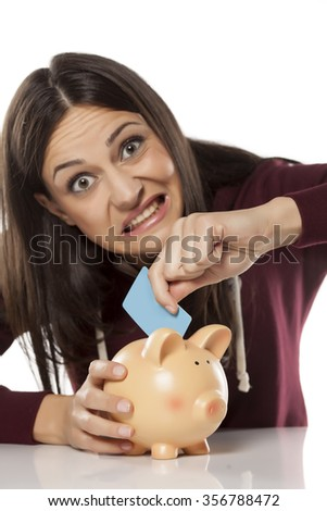nervous young woman putting a credit card in a piggy bank