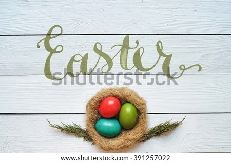 Nest colored eggs wreath on white wooden planks background. Easter greeting postccard template. Space for copy, text, lettering. - stock photo
