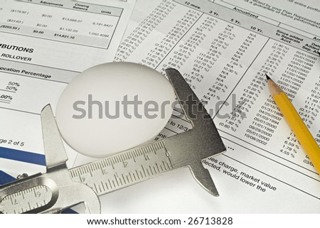 Nest Egg being measured against a background of 401K investment statements and documents. - stock photo