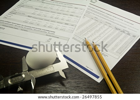 Nest egg being measured with 401K report as background with pencils on desk top. - stock photo