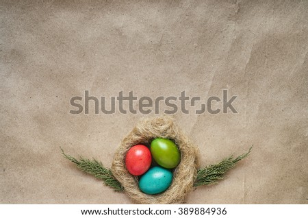 Nest with colored eggs on eco craft paper background. Easter postcard template. Space for text, copy, lettering. - stock photo