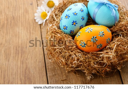 Nest with Easter eggs on the wooden table - stock photo
