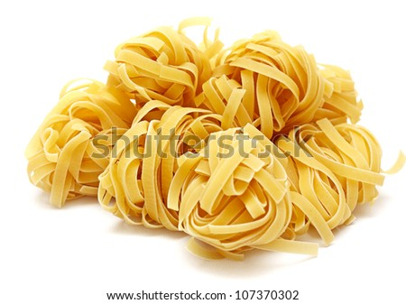 Nests of dry pasta tagliatelle on white background