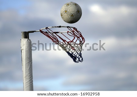 Netball about to go into the goal - stock photo
