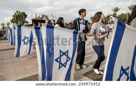 NETHANIA, ISRAEL - NOVEMBER 28, 2014: BNEI AKIVA youth group ceremony rehearsal with Israeli flags - stock photo