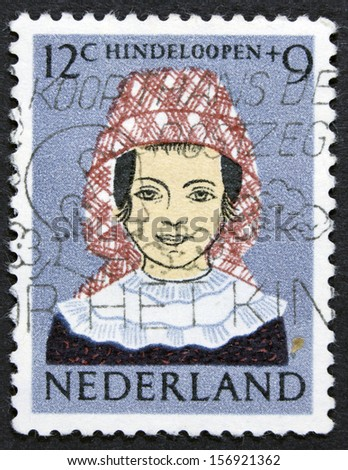 NETHERLANDS - CIRCA 1960: A stamp printed in Netherlands shows Girl in Regional Costume, Hindeloopen, circa 1960  - stock photo
