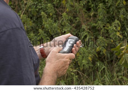NETHERLANDS-JULY 23,2015: Man holding a GPS receiver in his hand. Handheld GPS devices are used predominantly in the outdoor leisure industry for walking and hiking.