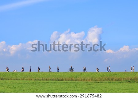 NETHERLANDS,MARKEN,OCTOBER 12,2014 : People walking on the road through a  dutch green meadow to the sea.This road is favorite for daily hiking for Marken's citizens and tourists (Marken,Netherlands)  - stock photo