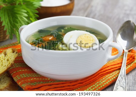 Nettle soup with eggs in the bowl on the table