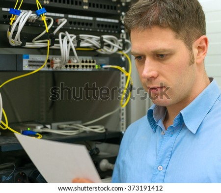 Network administrator with manual in server room. - stock photo