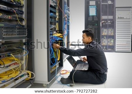 Network administrator with notebook computer and smartphone in hand sitting in data center room and working with networking device on rack cabinet
