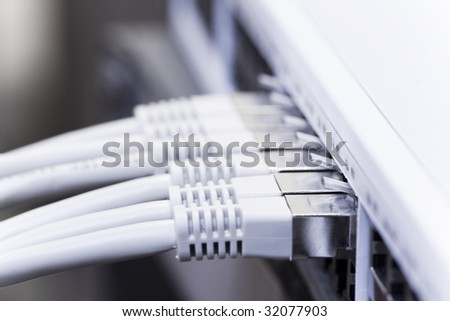 Network cables connected to a switch - stock photo