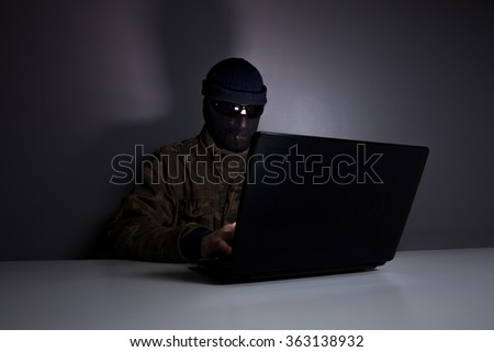 Network criminal man examining a laptop computer. The man has a camouflage jacket, sunglasses and balaclava. The photo is underexposed.