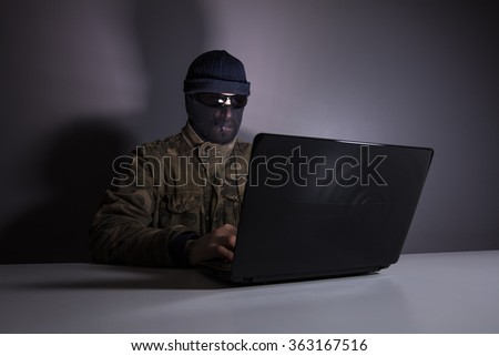 Network criminal man examining a laptop Computer. The man has a camouflage jacket, sunglasses, and balaclava. The photo is underexposed.