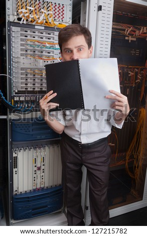 Network engineer in server room with documents folder - stock photo