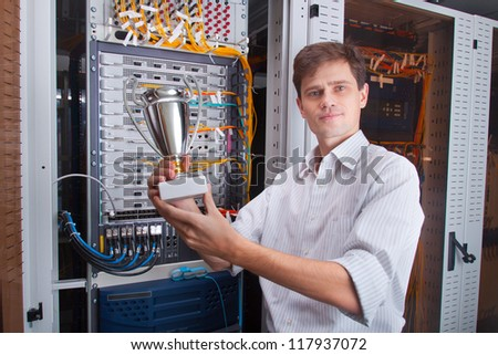 Network engineer in server room with the cup - stock photo