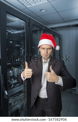 Network Engineer  in the server in Santa Claus hat show OK on colorize background - stock photo