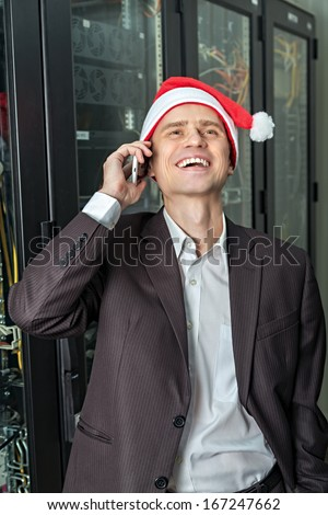 Network Engineer laughs in the server in Santa Claus hat with mobile phone