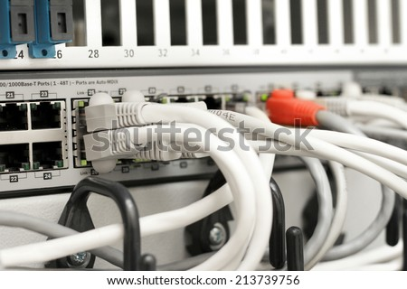 network hub and cables connected to servers in a datacenter - stock photo