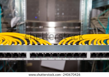 Network Patch Panel in a datacenter with network cables in front view - stock photo