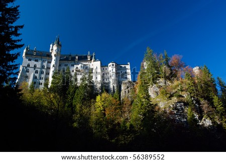 Neuschwanstein castle, bottom view of the south side of the castle with some shadow and forest in the foreground and clear blue sky in the background - stock photo