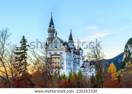 Neuschwanstein, Lovely Autumn Landscape Panorama Picture of the fairy tale castle near Munich in Bavaria, Germany with colorful trees in the morning hours - stock photo