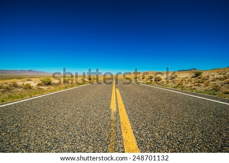 Nevada Backcountry Straight Rural Road. Nevada Highway and Clear Blue Sky. - stock photo