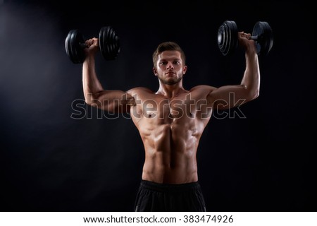 Never stopping. Horizontal shot of a young shirtless fitness man exercising rising up dumbbells against black background