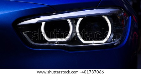 New aggressive headlight by night. Car detail. The front lights of the blue car, in sports car developed by model 2016. Car's light. - stock photo