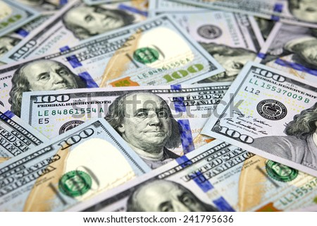 New American 100 dollar bills scattered randomly with the portrait of Benjamin Franklin uppermost - stock photo