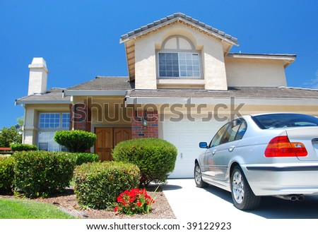 New American dream home with a beautiful blue sky in background and brand new car parked outside - stock photo